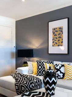 Black, yellow, and white in bold patterns make a big statement in this living room. We love the visual interest of the mixed patterns!