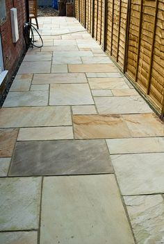 Celtic Bronze sandstone paving stones make an attractive yet practical walkway next to your house.