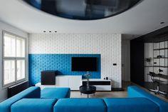 Jednotná linka bytu se prolíná v modré barvě, která je použita například v malbě na cihlové stěně v obývacím pokoji a na sedací soupravě.