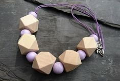 This necklace features polygon shaped wooden beads in a natural finish. In between these are smaller round wooden beads in a pretty shade of lilac. All of them have been strung onto two lengths of purple cotton cord. A heart shaped toggle clasp has bee. Polygon Shape, Lilac, Purple, Geometric Necklace, Organza Gift Bags, Handmade Jewellery, Wooden Beads, Natural Wood, Heart Shapes