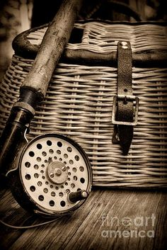 Still life showing a vintage fishing creel and vintage fly reel in black and white.