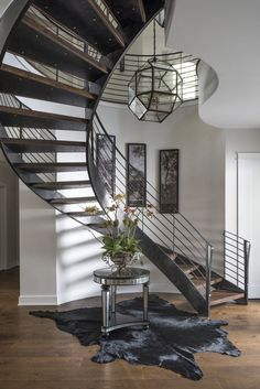 As you enter this farmhouse, your first view is the custom metal staircase that graciously curves up to the second floor. The sinuous curves of the metal frame is accented with reclaimed wood treads salvaged from a 100 year old barn. Three pendants in various sizes hang from the second floor. On the wall of the staircase hangs a triptych of a 100 year old photograph of the street that the home is built on.