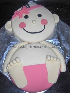 """baby shower cake - The head and body are both white 9"""" round cakes decorated in fondant. The diaper and hair bow are colored with pink neon food coloring. The body and face are peach and the hair and eyes are black."""