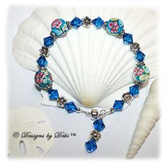 Designs by Debi Handmade Jewelry Oceans of Aloha Blue, Pink and Yellow Aloha Floral Round Beads, Silver Flowers and Swarovski Crystal Capri Blue Bicones Bracelet with a Silver Magnetic Clasp $37