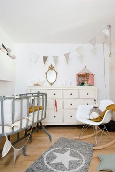 Beautiful bassinet and Eames Rocker add to Scandinavian style of the room