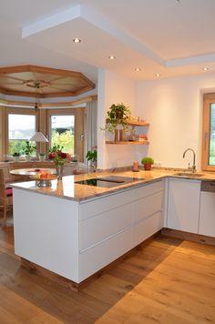 Küche in Eiche- Altholz mit Spiegelglanz Fronten Grifflos und kombiniert mit einer Arbeitsplatte aus Granit.