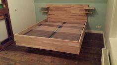 Zwevend tweepersoonsbed van hout. Eigen ontwerp en met de hand gemaakt.