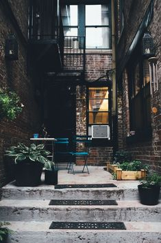 Courtyard with Black Walls, exposed brick and turquoise cafe set | The Good Hacienda | curated by Hilary