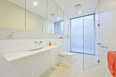 The all-white structured design of this bathroom makes it unusual. Has that open feel. love the all white with a pop of color in the towels and candles! #inspiration