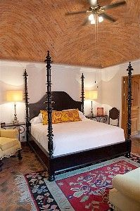 The elegant master suite with boveda ceiling and handmade Portuguese-style bed