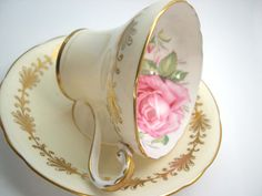 Beautiful antique tea cup and saucer made by Aynsley England Yellow tea cup set with large pink rose inside the cup. The backstamp date this cup 1939+ The rims are gilt. Cup Measures: 2 5/8 high & Saucer Measures 5 1/2 diameter Very good conditon, no chips, no cracks, no gold loss,