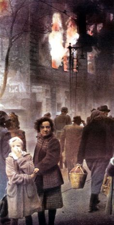 A house is burning after a bomb attack on Berlin. circa 1944. People are walking along the street where two young girls are posing for the photographer. More than 300 bombardments by the British Royal Air Force (RAF) and the United States Army Air Forces took place in the period from June 1940 to the end of the war in 1945. Berlin, Germany. (Photo by Galerie Bilderwelt/Getty Images)