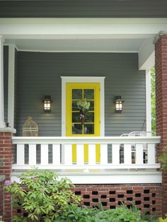Gray siding, white trim, bright yellow door.