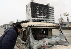 Reuters / Thursday, December 04, 2014  A man looks into a burnt-out car near the Press House building, a local media agency, after a gun fight between gunmen and policemen in the Chechen capital Grozny.