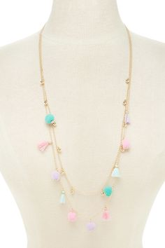 A high-polish layered necklace featuring pom pom and tassel charms, a beaded design, and a lobster clasp closure.