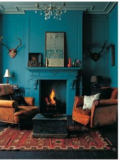 Intense deep teal walls and fireplace with earth brown and red furniture and acc.- Intense deep teal walls and fireplace with earth brown and red furniture and accessories and antiques plus antlers