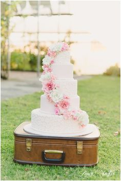 Romantic pink, lace and roses wedding cake - live the suitcase instead of a cake stand!