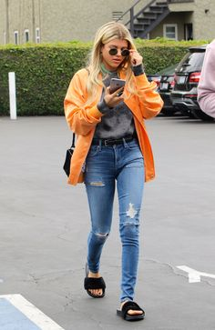 Sofia Richie wears an orange bomber jacket, grey sweater, blue jeans, and fur slides