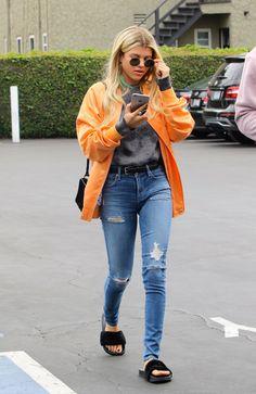 Sofia Richie wears an orange bomber jacket, grey sweater, blue jeans, and fur slides