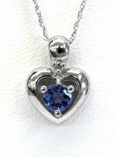 Ladies 14kt white gold gemstone and diamond pendant. Mounted in pendant is a round cut tanzanite and 1 brilliant round cut diamond weighing approximately .01ct. Pendant comes with an 18 inch white gold chain.