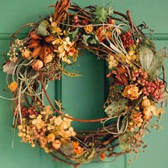 Dried Flower Vine Wreath Three groupings of dried hydrangea, grasses, berries, and blossoms are attached with wire or hot glue to this grapevine wreath base.