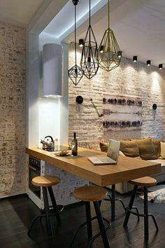 cuisine bois clair, canapé avec des grands coussins en beige, sol au revêtement en parquet PVC noir, petit tapis blanc devant le canapé, cuisine ouverte sur le salon