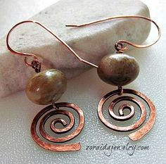 Beautifully hammered copper spirals, forged by hand, dangle beneath large stone beads in these wonderfully rustic earrings.  Swirls of olive, brown and pale green dance across these large approximatel