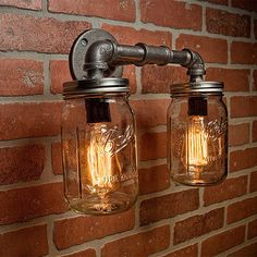 A handmade industrial chic two light sconce that is sure to add a truly charming accent to any home. This unique and re-imagined blend of metal pipe fittings and mason jars create a unique light that will surely add a warm and welcome atmosphere to your home or business. Features a quart size Ball mason jar. This is sure to become the topic of conversation among guests, friends, family or clients.  All TMG-DZN fixtures will accept most Incandescent, CFL or LED bulbs. Light socket rated for…