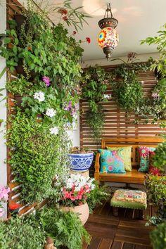 üppige Balkonpflanzen vertikaler Garten und bunte Balkonmöbel
