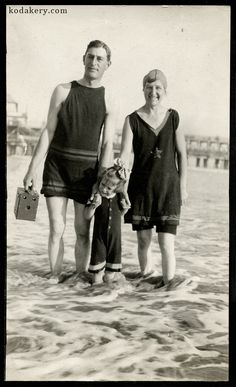 Vintage snapshot of a 1920s family in the surf, with the man holding a period box camera