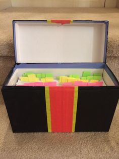 Clue box for Amazing Race party. Painted old card box with black paint, added red and yellow masking tape stripes.