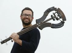March 28, 2013: Mexican artist Pedro Reyes poses with one of his artworks, a bass guitar made out of recycled guns, at the Lisson Gallery in...