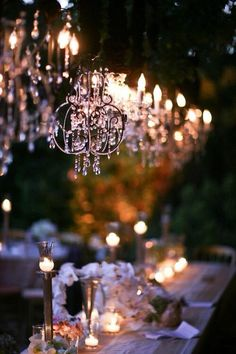 Chandeliers hanging from trees over dining tables at an outdoor wedding...absolutely stunning. #wedding #lighting