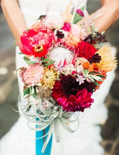 Fiesta-inspired bouquet with protea, peonies + air plants
