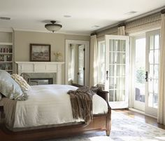 fireplace in bedroom with french doors--love this look but would change the boring light fixture above the bed.