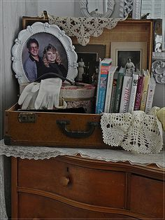 Cute way to use an old suitcase!  I love the old pics and books.