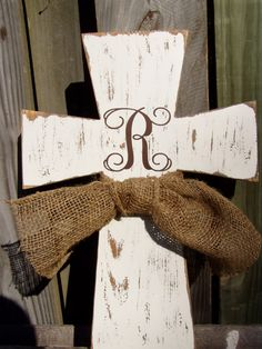 """Monogram Wooden Distressed Cross. Beautiful monogram distressed wooden cross. Handcrafted from reclaimed wood. This cross has been hand painted with an antique cream latex paint and then distressed by hand using a staining technique. The chocolate monogram letter has been carefully crafted from a commercial grade vinyl in script font, and adorned with a natural burlap ribbon. This cross measures approximately 16.5""""h x 11.5""""w."""
