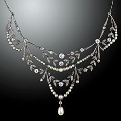 A regal, yet feminine original Edwardian garland necklace, circa 1900. Swags of natural creamy white pearls drape in between sparkling diamond set, foliate style garlands of platinum over gold. The back neck piece is composed of gracefully curved and milgrained knife edge bars punctuated with bezel set rose cut diamonds. A rare and gorgeous treasure for festive occasions.