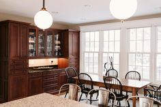 Just past the kitchen, you'll find this casual dining room with black Windsor chairs and a rectangular wood dining table. A large, dark wood built-in hutch offers plenty of storage for dishes and glassware.