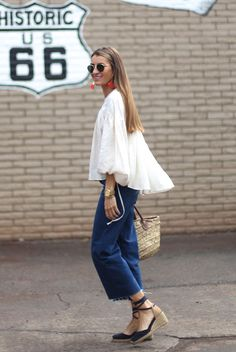 Street Style - The Top Blogger Looks Of The Week: Fashion blogger 'Bartabac' wearing a white v-neck ruffle top, denim culottes, navy espadrille wedges and a basket bag. Summer outfit, comfy outfit, beach outfit, travel outfit, vacation outfit, getaway outfit, street chic style, boho chic outfit, boho outfit, boho chic style.