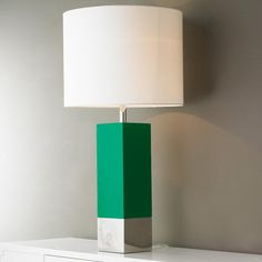 Tall Chrome and Lacquered Modern Table Lamp This tall green lacquered square column is anchored with a polished chrome band to create this modern table lamp. Topped with a white linen shade and acrylic cube finial, the combination is stunning. The kelly green base challenges the modern simplicity this lamp has to offer with its bold color statement