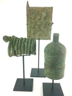 These African bronze pieces have a large copper content which creates the beautiful and much sought after verdigris patina.   A bell with ornate accents, a snake like coiled currency and a miniature representation of a granary door all are museum mounted on metal stands. A special collection.