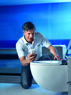 Jan-Peter Tewes, Master of Technology, sets the water jet's temperature, pressure and direction with the GROHE Sensia® IGS remote control.