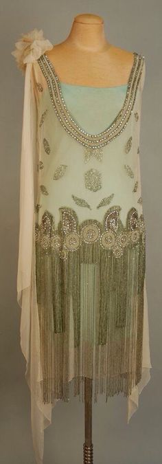 """JEWELED FLAPPER DRESS with BEADED FRINGE, 1920's. White chiffon with deep """"U"""" neckline front and back trimmed with a wide band of pearl, rhinestone and crystal bead medallions, wide jeweled hip band with graduated long beaded fringe"""
