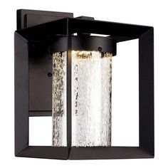 Clean-lined design and geometric silhouette define this chic one-light outdoor wall lantern. Made steel in a textured black finish, this charismatic design includes a rectangular backplate, an angular arm, and seeded glass cylindrical shade within a square frame. For an understated seating arrangement for you and your better half to enjoy a starless night in, place a glass-top side table between two hoop chairs with tubular legs, then mount one of these lights on each side of sliding glass…