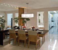 Na sala de jantar, destaca-se o espelho de fundo com laterais em madeira de demolição, fazendo composição com a mesa de tampo de vidro negro, dando mais amplitude ao ambiente, que é integrado ao living e ao home.