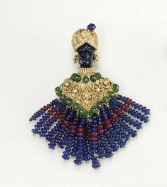 A MULTI-GEM BLACKAMOOR BROOCH  The carved hardstone blackamoor, with a fluted gold and circular-cut diamond turban, accented by a cabochon sapphire, wearing diamond collet and gold wirework ear pendants, to the tunic of similar design, with cabochon emerald borders, suspending a ruby and sapphire bead fringe, mounted in gold