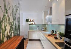 mintgrüner Glas Spritzschutz, weiße Fronten und beige Quarz Arbeitsplatte