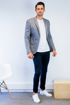 business professional attire, man with slicked back hair, white t-shirt and grey blazer, dark blue trousers and white sneakers