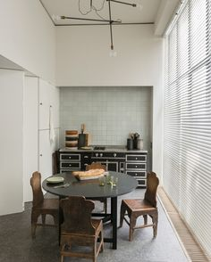 Home of Belgian architect Vincent Van Duysen in Antwerp Delft tile lines the kitchen, furnished with a La Cornue stove, Chinese farmer's chairs and a light fixture from Workstead in Brooklyn. Ceramics designed by Van Duysen are stacked on the stove.